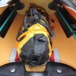 a drybag strapped to anchor points in a kayak's cockpit