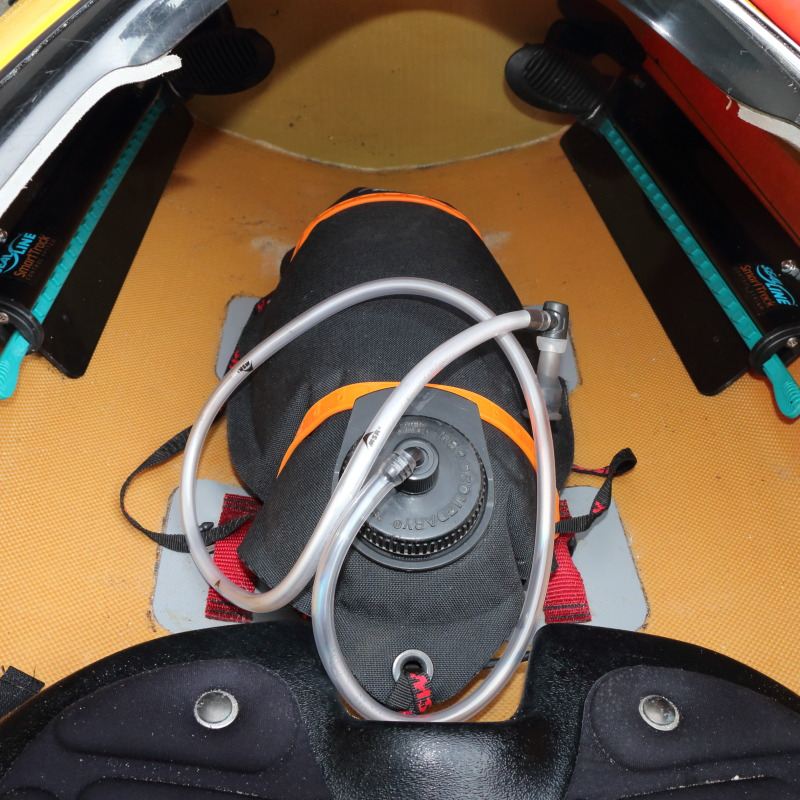 a waterbag with drinking hose strapped to the floor of a kayak's cockpit