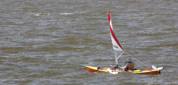 A single sea kayak equipped with a Hobie sail and amas.