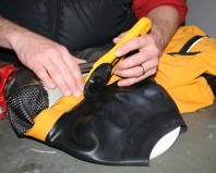 Cutting away the damaged neck seal of a drysuit