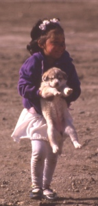 Inuit girl carrying a husky puppy