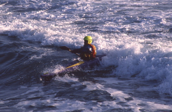 A kayaker surfs a breaking wave