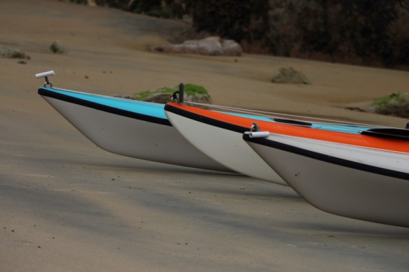 the bows of three sea kayaks in a row