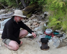 a camper cooks on a portable woodstove