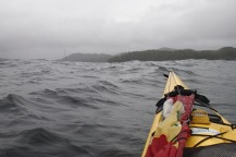 View from the kayak: the tip of a sailboat mast barely visible beyond a swell