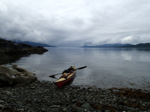 A sea kayak pulled up on a cobble beach.