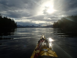 View over the kayak bow: low clouds backlit by the sun.