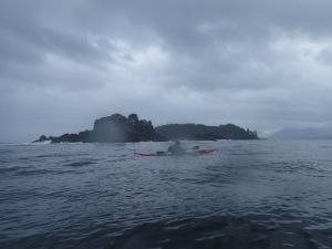 sea kayaker off wave-swept rocks
