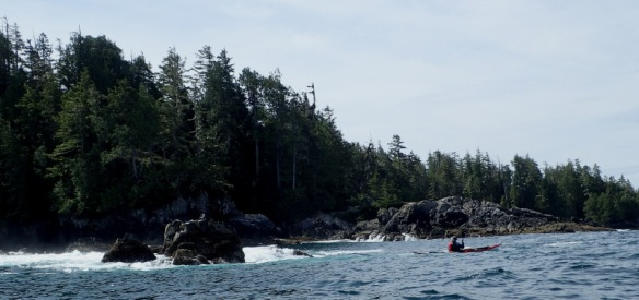 a sea kayaker paddles near surf breaking on a rocky shore