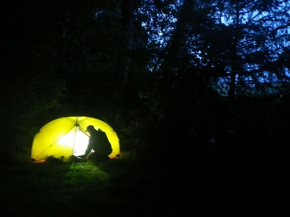 By the light of the moon, a camper enters an iluminated tent