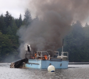 an anchored boat on fire