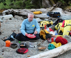 a kayaker cooks steak strips on a campstove
