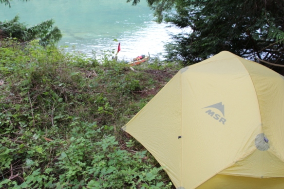 looking over a tent to a sea kayak at the water's edge