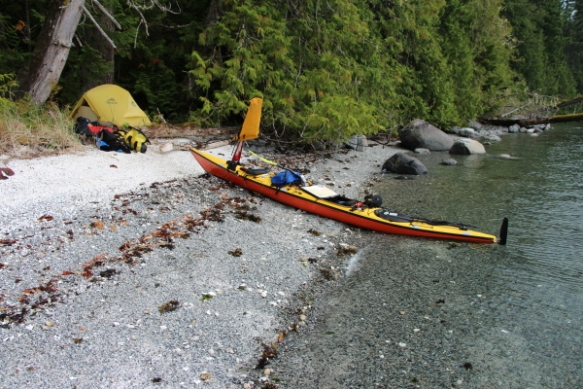 A beached sea kayak with a tent in the background