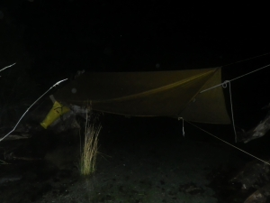 a camping hammock at night suspended over water