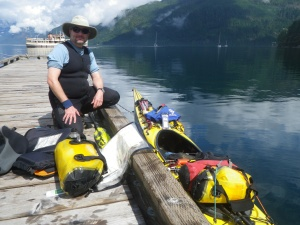 a kayaker kneels on the dock beside his boat