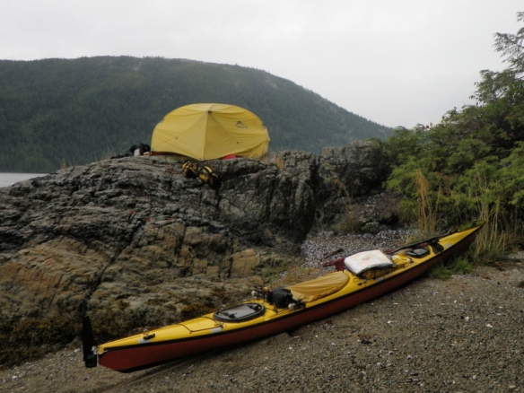 a sea kayak on the shore with a tent in the background