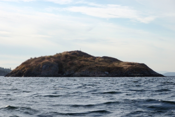 A rocky islet with a memorial cross