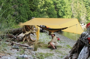a camper kneels next to his tarped hammock