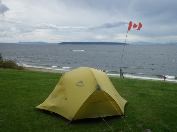 a tent next to a flag pole in strong wind