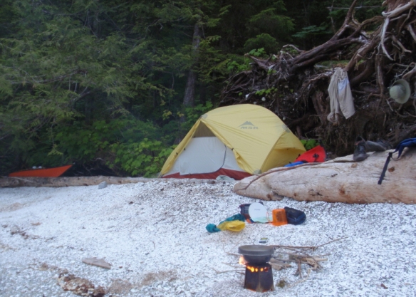 a tent and woodstove on a shell beach