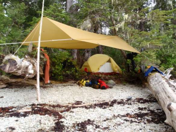 a tent and a tarp rigged at the shore's edge