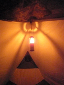 a candle lantern hanging inside a tent