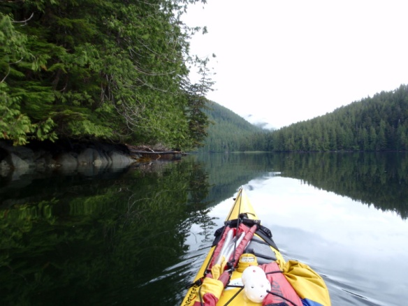 a calm inlet viewed over the bow of a kayak