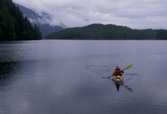 a kayaker paddles across a calm and cloudy inlet