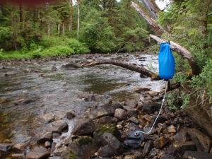 a gravity fed water filteration bag next to a creek