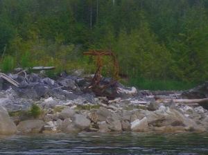 rusty mining equipment on a rocky shore