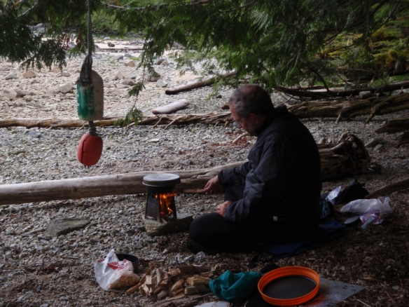 a camper stokes a portable wood-fired campstove