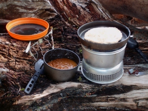 a campstove with baked beans and bannock