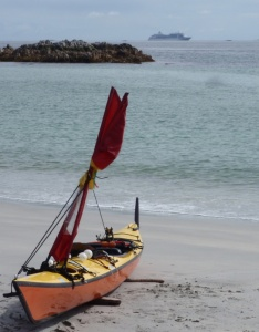 a sea kayak landed on a beach, with a cruise ship in the background