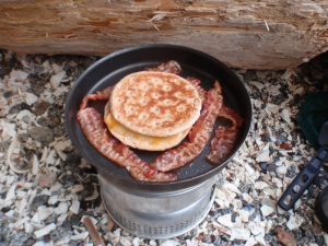 toasted cheese muffins and bacon on a campstove