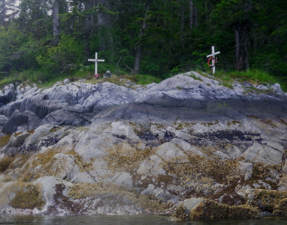 a pair of white memorial crosses on the shoreline