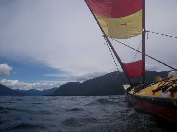 a sea kayak under sail, viewed from water level