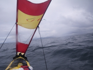 a kayak under sail in a high wind