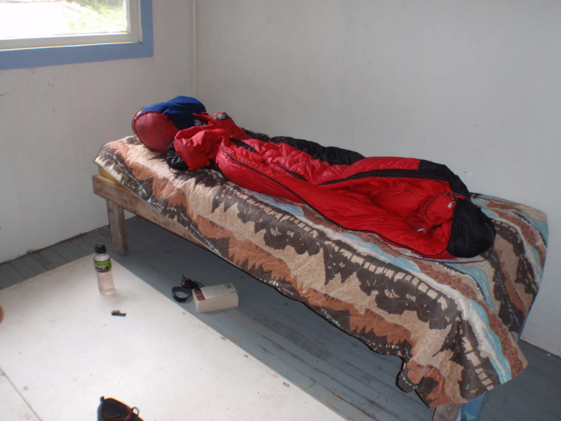 a single bed with a sleeping bag on top