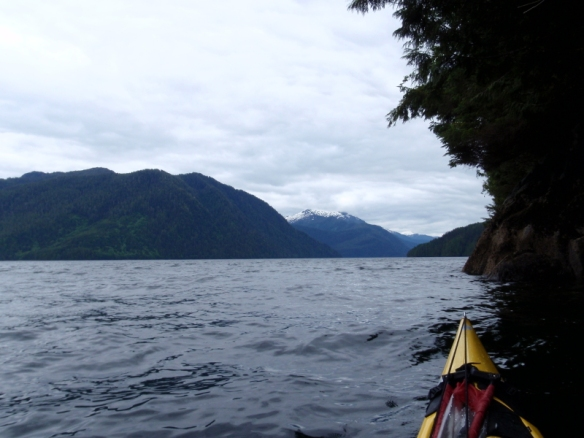 a paddler's eye view of a sea kayak heading down a fiord