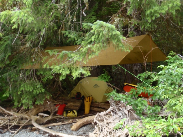a tarp and a tent rigged on a stony beach