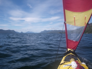 A sea kayak sailing north. Swindle Island and Cone Island, British Columbia are visible on the horizon.