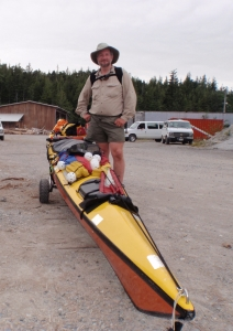a kayaker next to his boat on wheels