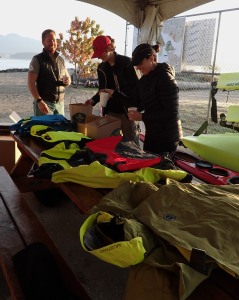 paddlers admire a table of sea kayak clothing and equipment