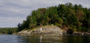 a sea kayak paddles beneath Kanaka Bluff, Portland Island (Princess Margaret Island) Gulf Islands National Park