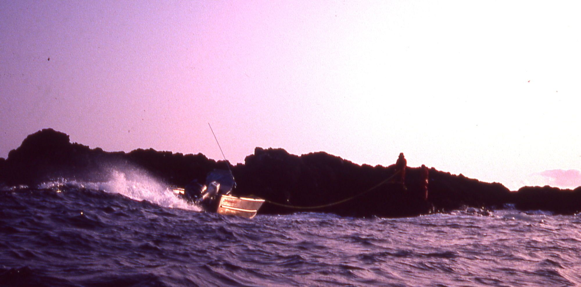 two men on a reef use a line to haul in their boat