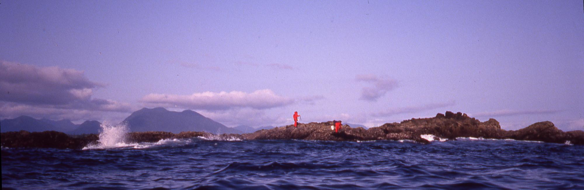 two men in red floater suits standing on Verbeke Reef in the Broken Islands group, British Columbia