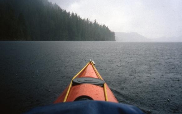 A sea kayak makes its way through heavy rain
