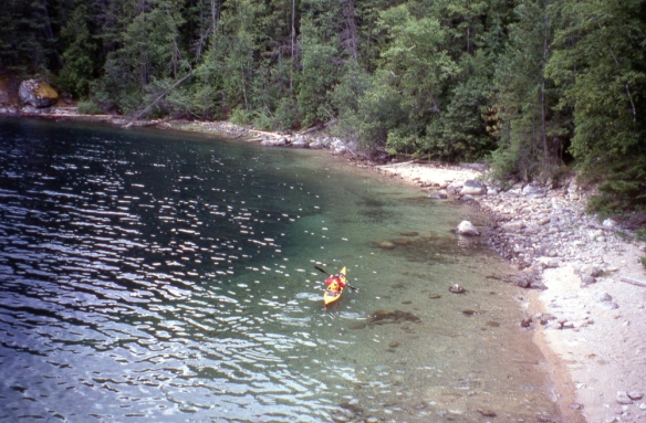 a kayaker paddles near the shore of Slocan Lake