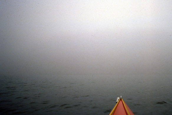 the bow of a sea kayak making its way through fog